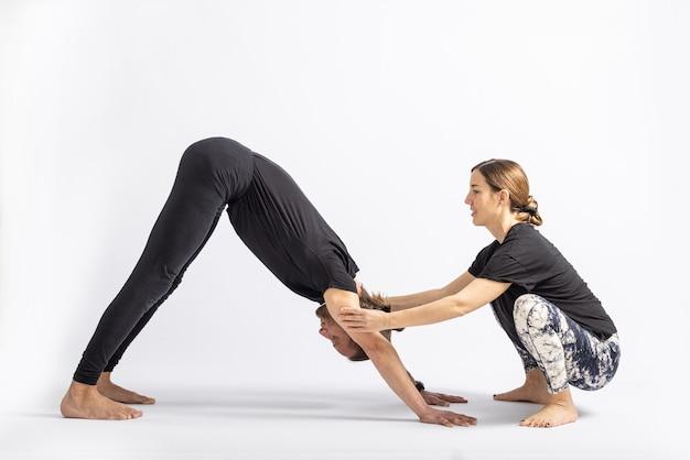 Yogaleraar die houding corrigeert aan haar student die op witte achtergrond wordt geïsoleerd