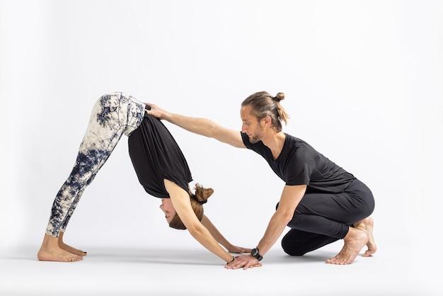 Yogaleraar die houding corrigeert aan zijn student die op witte achtergrond wordt geïsoleerd