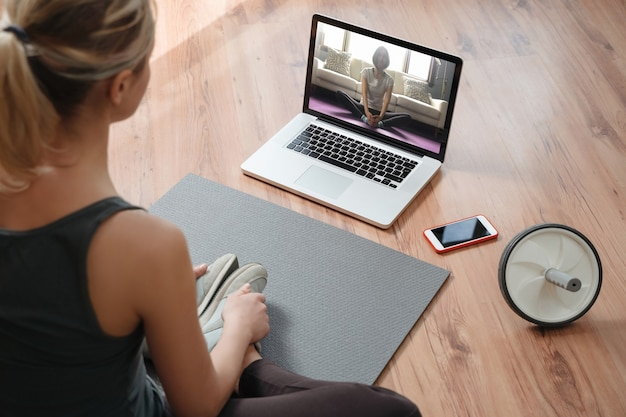 Yogaleraar die virtuele les thuis uitvoert op een videoconferentie. jonge mooie vrouw die een online yogales doet