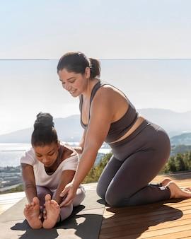 Yogaleraar die vrouw helpt met het volledige schot van de pose