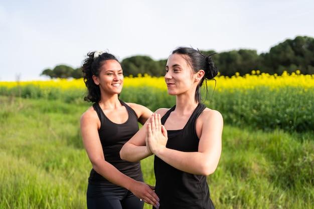 Yogaleraar geeft les aan student die net begint in de natuur