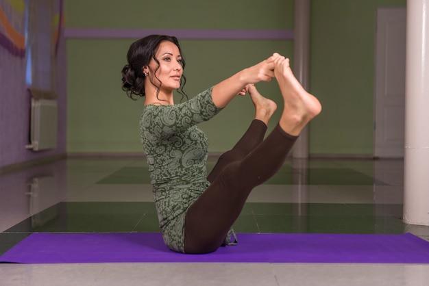 Yogaleraar uitvoeren van yoga in de sportschool.