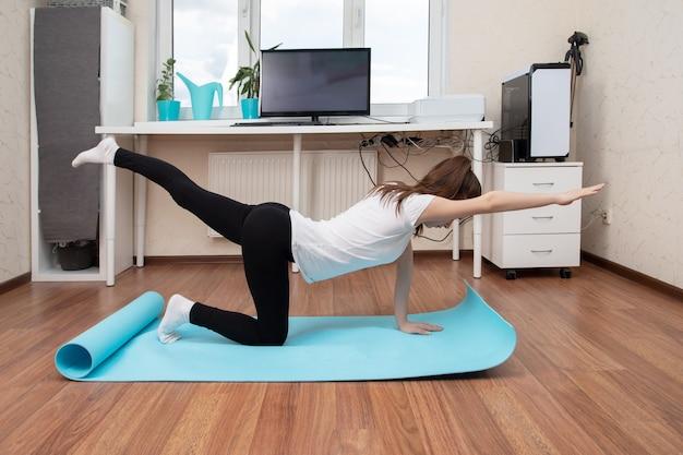 Yogalessen aan huis. het meisje houdt zich bezig met videolessen via internet