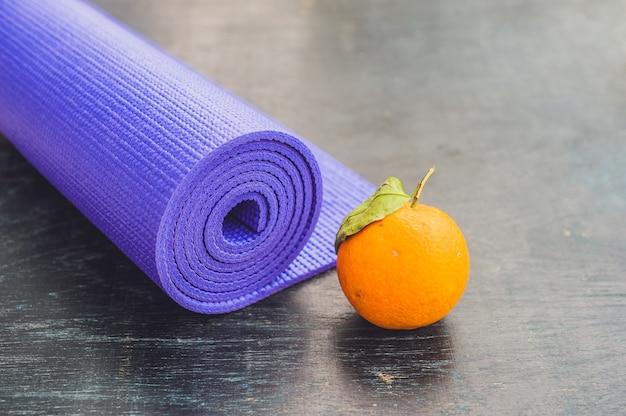 Yogamat en sinaasappel op een houten achtergrond