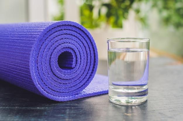 Yogamat en water op een houten achtergrond