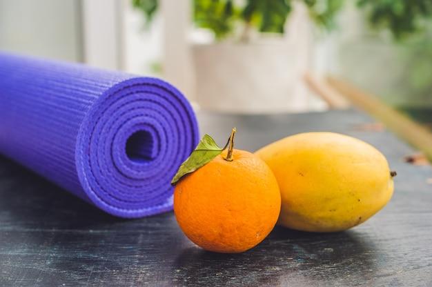Yogamat, sinaasappel en mango op een houten achtergrond