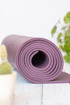 Yogamat, slechte houten kralen op wit hout. essentiële accessoires voor het beoefenen van yoga en meditatie.