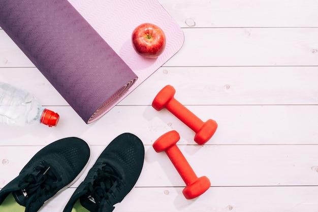 Yogamat, sportschoenen, halters en een fles water op blauwe achtergrond. concept gezonde levensstijl, sport en dieet. sportuitrusting. ruimte kopiëren