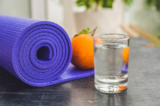 Yogamat, water, sinaasappel en mango op een houten oefening als achtergrond voor yoga