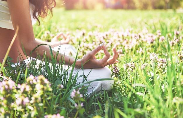 Yogameditatie in een park op het gras is een gezonde vrouw in rust.