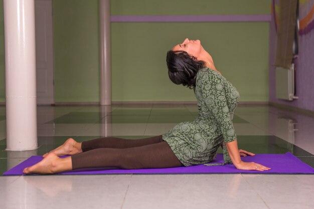Yogameester die yoga-oefeningen doet in een studio