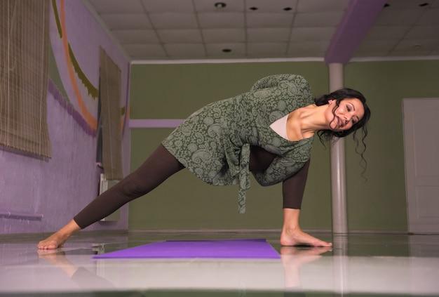 Yogameester strekt zich uit over yogahoudingen in de fitnessklasse