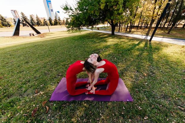 Yogameisjes in stadspark oefenen zich uit in pose urdhva mukha shvanasana, opwaarts gerichte hond. groep mensen mediteren op zonnige zomermorgen in park bij dageraad onder begeleiding van instructeur