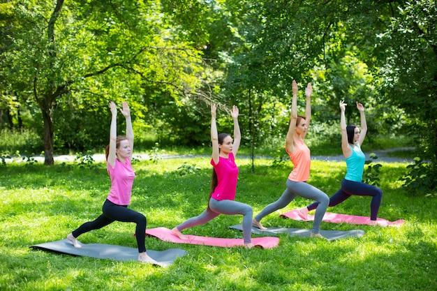 Yogamensen die oefeningen in het park doen