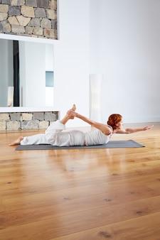Yogaoefening in houten vloergymnastiek en spiegel