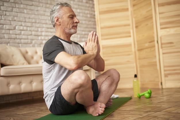 Yogaoefeningen thuis meditatie van senior man.