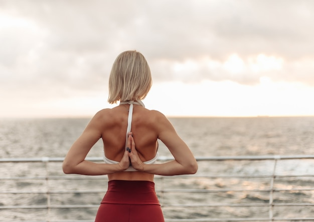 Yogapraktijk bij zonsopgang jonge vrouwelijke yogi die namaste achter de rug maken