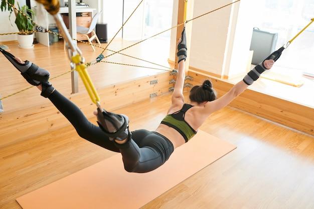 Yogatrainer die oefening tonen aan vrouw het hangen op trapeze