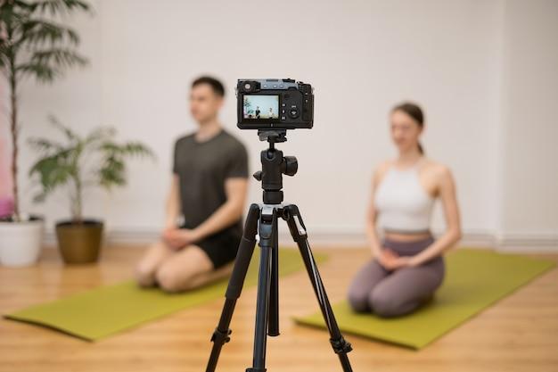 Yogatrainer die online trainingsprogramma onderwijst in thuisstudio achter camera. sportinstructeurs die yogahoudingen tonen, uitleggen, nog wat tips geven.