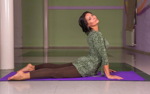 Yogatrainer maakt asana-oefeningen in de sportschool.
