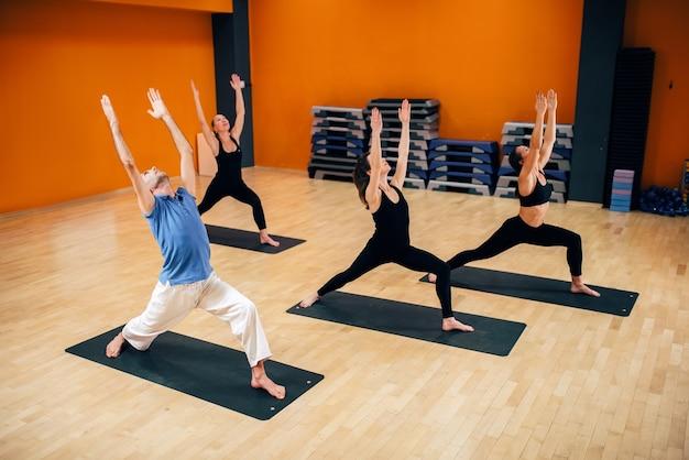 Yogatraining klasse, vrouwelijke groep met mannelijke instructeur in actie in de sportschool. yogi oefenen binnen