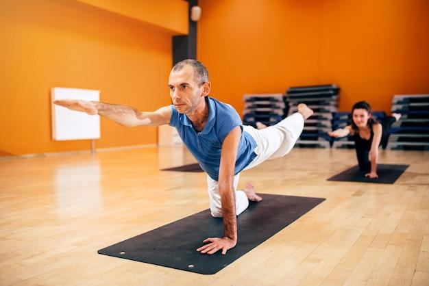 Yogatraining, vrouwelijke groep met instructeur, vetverbranding, trainen in de sportschool. yogi binnen