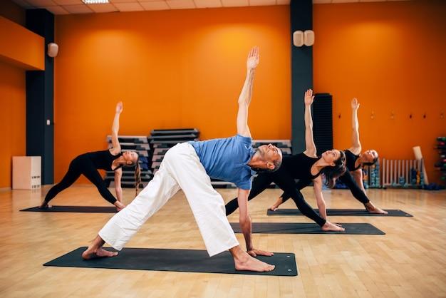 Yogatraining, vrouwelijke groep met trainer in beweging, trainen in de sportschool. yogi oefenen binnen