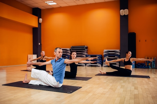 Yogatraining, vrouwelijke groepstraining met mannelijke trainer in de sportschool. yogi oefenen binnen