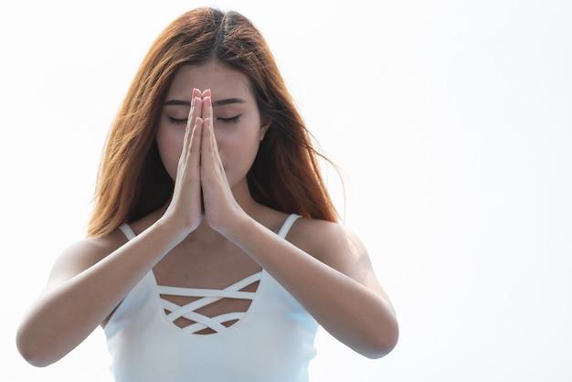 Yogavrouw die met holdingshanden samen op witte achtergrond mediteren.