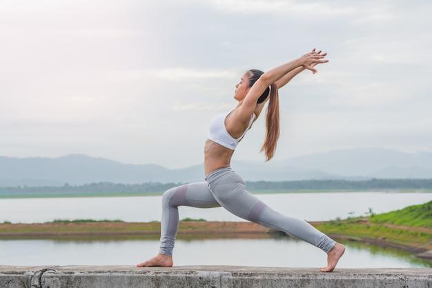 Yogavrouw die oefening doen bij de rivier in de ochtend.