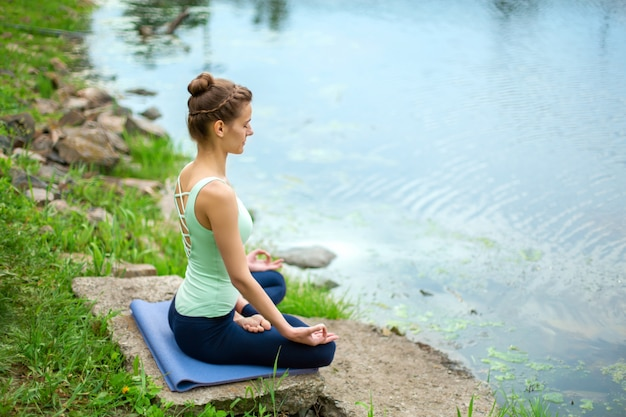 Yogavrouw het beoefenen van yogales, ademhaling, meditatie, oefening ardha padmasana, halve lotus pose met mudra-gebaar, close-up in de zomer op de natuur tegen het water