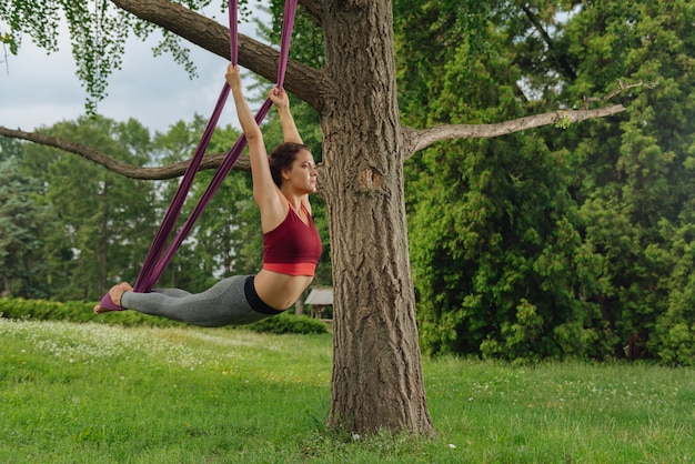 Yogavrouw voelt zich gewoon perfect terwijl ze haar rug strekt en haar favoriete vliegyoga beoefent