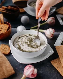 Yoghurt dovga met groenen binnen ronde witte plaat samen met brood loafs eieren op grijze tafel