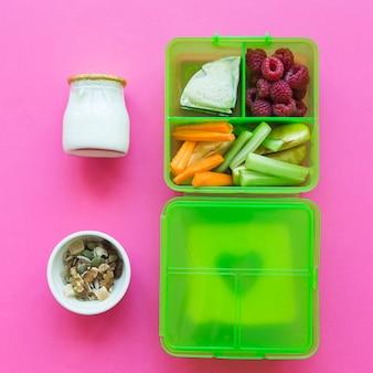 Yoghurt en muesli dichtbij lunchbox met gezond voedsel