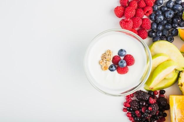 Yoghurt in de buurt van fruit en bessen