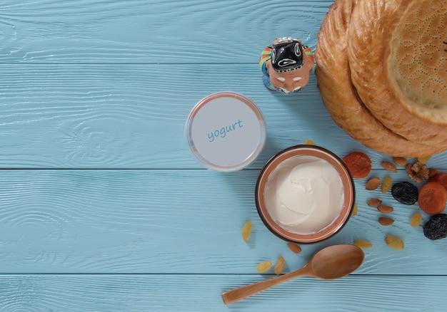 Yoghurt in een plastic verpakking met een platte cake op een blauwe houten achtergrond gezond eten concept