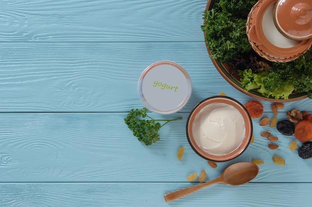 Yoghurt in plastic verpakking met groene salade op blauwe houten achtergrond gezond eten concept