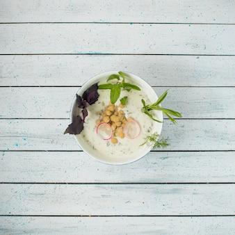 Yoghurt met bonen, kruiden en rode basilicum in een kom.