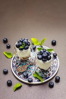 Yoghurt met bosbessen en chiazaad op snijplank