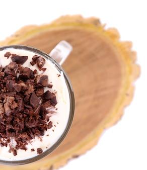 Yoghurt, met chocoladeroom, gehakte chocolade en muesli geserveerd in glazen pot, op een houten bord, geïsoleerd op wit