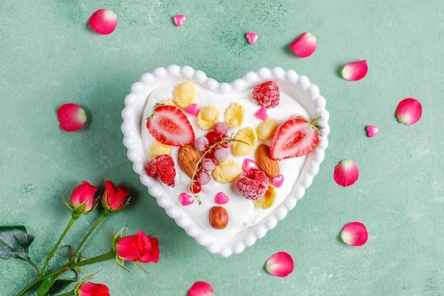 Yoghurt met cornflakes en bessen in een hartvormige kom.