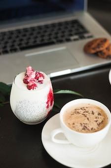 Yoghurt met frambozen; koffiekopje en cookies op laptop tegen zwarte achtergrond