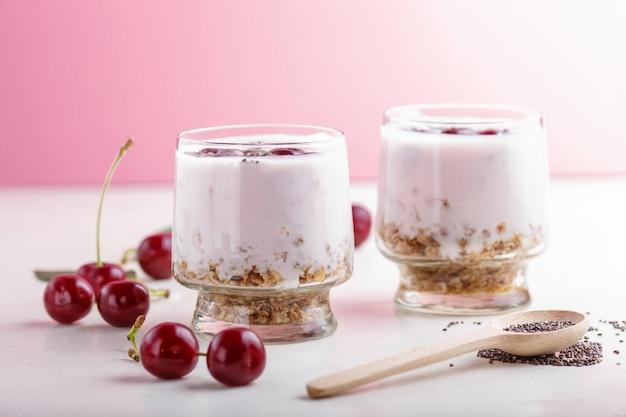 Yoghurt met kersen, chiazaad en granola in glas met houten lepel. zijaanzicht.