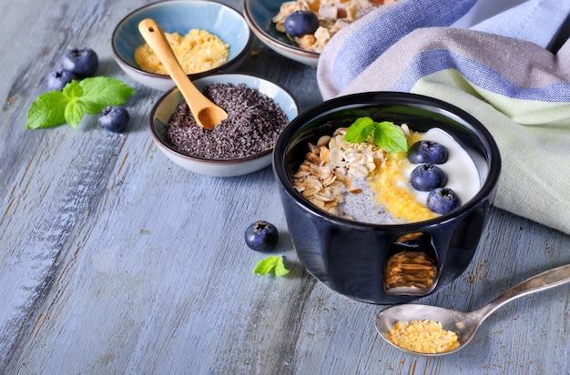 Yoghurt met muesli, bosbessen, maanzaad, munt en gemalen cornflakes geserveerd in zwarte glanzende kom