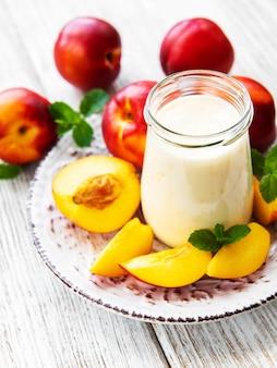Yoghurt met verse nectarines op een witte houten tafel