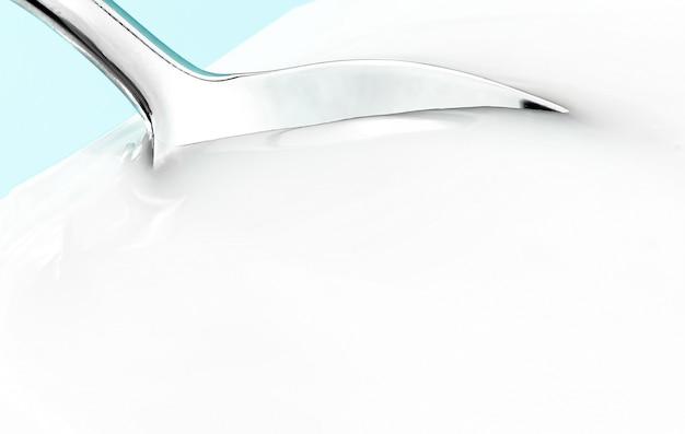 Yoghurtkop en zilveren lepel op muntachtergrond witte plastic container met verse melk van yoghurtroom...