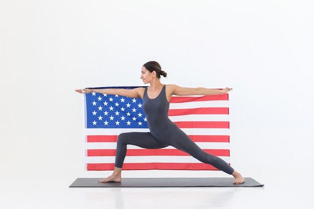 Yogi vrouw beoefenen van yoga staande op mat met amerikaanse vlag, oorlog pose. 4 juli onafhankelijkheidsdag concept