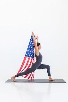 Yogi-vrouw die yoga-oefeningen beoefent die op een mat staan op een witte scène met een vlag van amerika