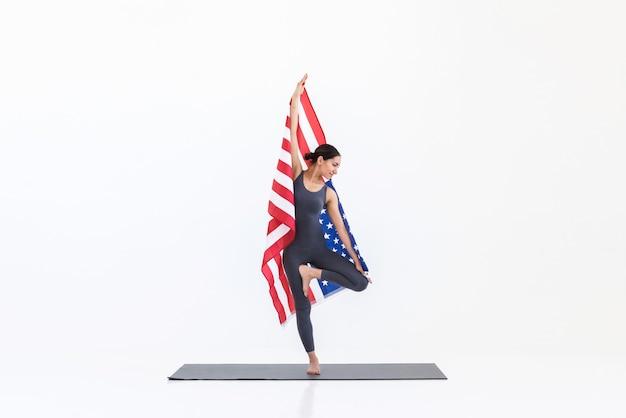 Yogi-vrouw die yoga-oefeningen doet terwijl ze op de mat staat met de amerikaanse vlag. 4 juli concept van de onafhankelijkheidsdag van de vs
