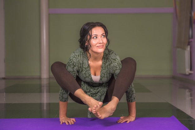 Yogi vrouw die zich uitstrekt in yoga in de sportschool./yoga meisje uitvoeren van yoga houdingen.